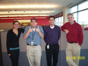 "Here are my coworkers and I (I believe all UC grads) with the Virginia Tech hat.  I'm making the ""thumbs up"""
